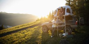 Couple camping, relaxing at SUV rooftop tent in sunny, idyllic field, Alberta, Canada