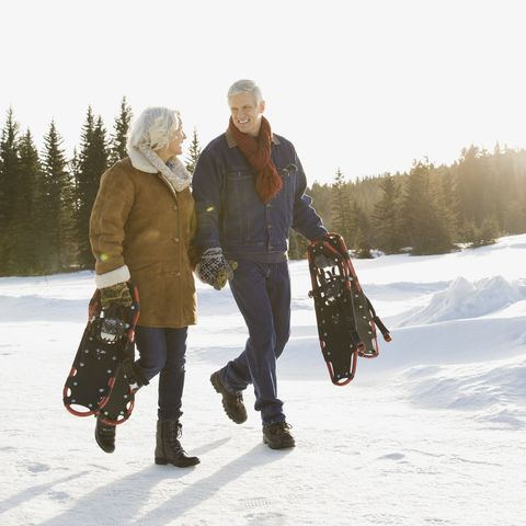 winter date ideas -Couple carrying snowshoes outdoors