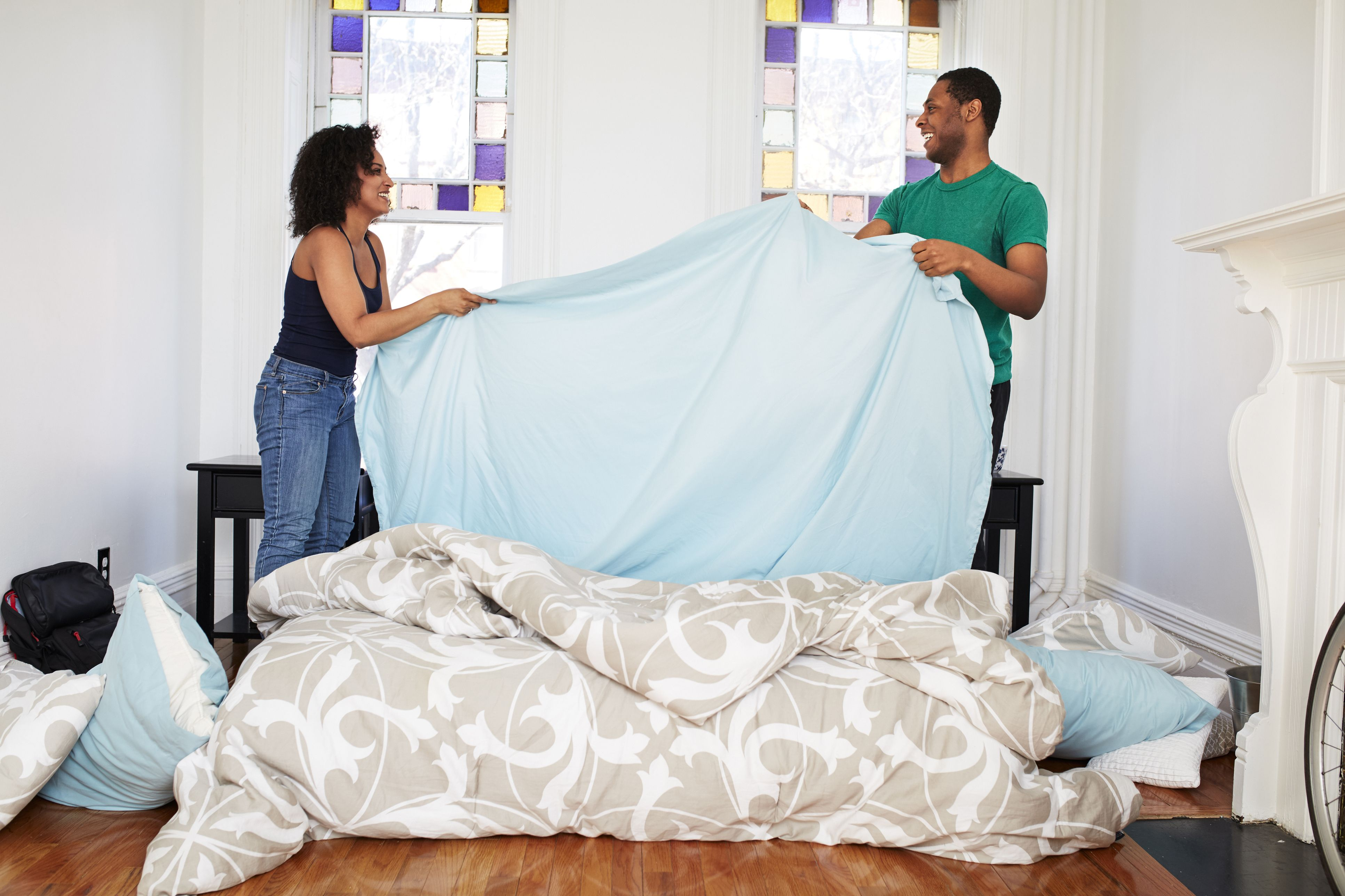 High Quality Couple Changing Sheets On Bed
