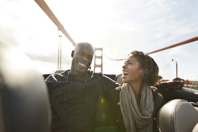 couple cheering and laughing on the backseat of convertible car