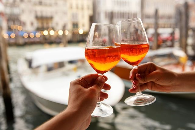 couple clinking glasses with spritz in venice, italy