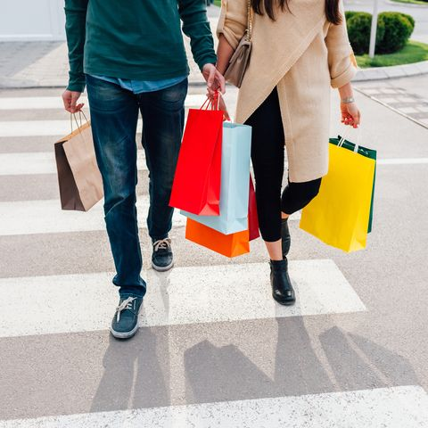 Couple crossing the street with shopping bags