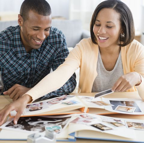 winter date ideas - Couple drinking red wine and looking at photographs