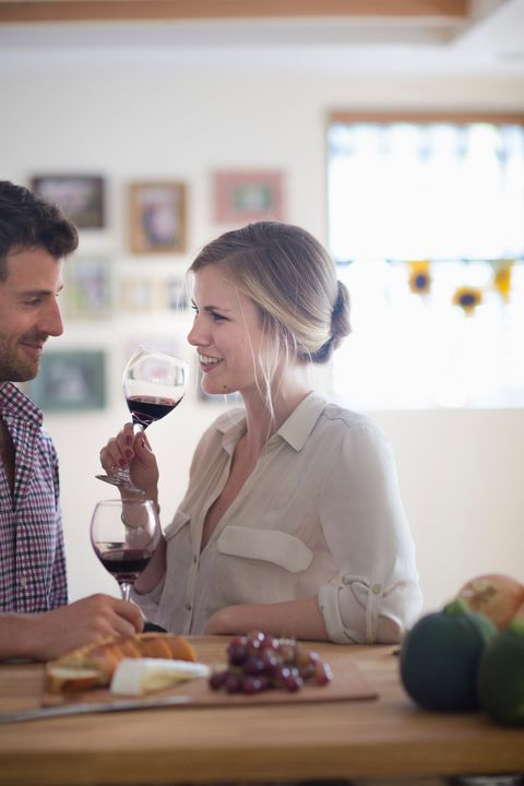 couple drinking red wine at dinner table