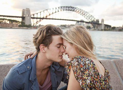 couple embracing in front of Sydney Harbour Bridge