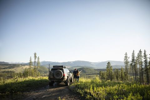 Couple enjoying overland adventure, looking at remote mountain view next to SUV, Alberta, Canada