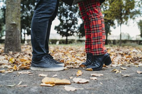 Couple face to face in autumn park, surface level view of legs