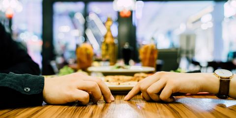 Couple going on a first date and attempting to hold hands during a dinner date at a restaurant