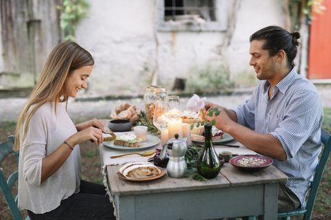 Couple having a romantic candelight meal next to a cottage
