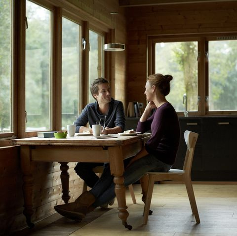 couple having breakfast at table in cottage
