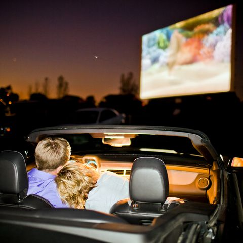 a couple having fun in their car at a drive in theater