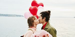 Couple holding heart shaped balloons kissing while exploring city