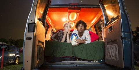 couple holding popcorn while sitting in camping van during drive in movie