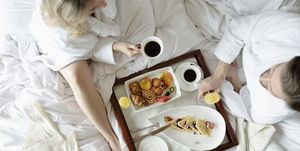 Couple in bathrobes enjoying breakfast in bed in luxury hotel, enjoying romantic weekend