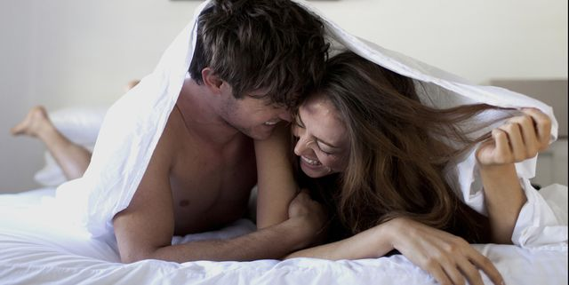 couple in bed laughing hiding under white sheets