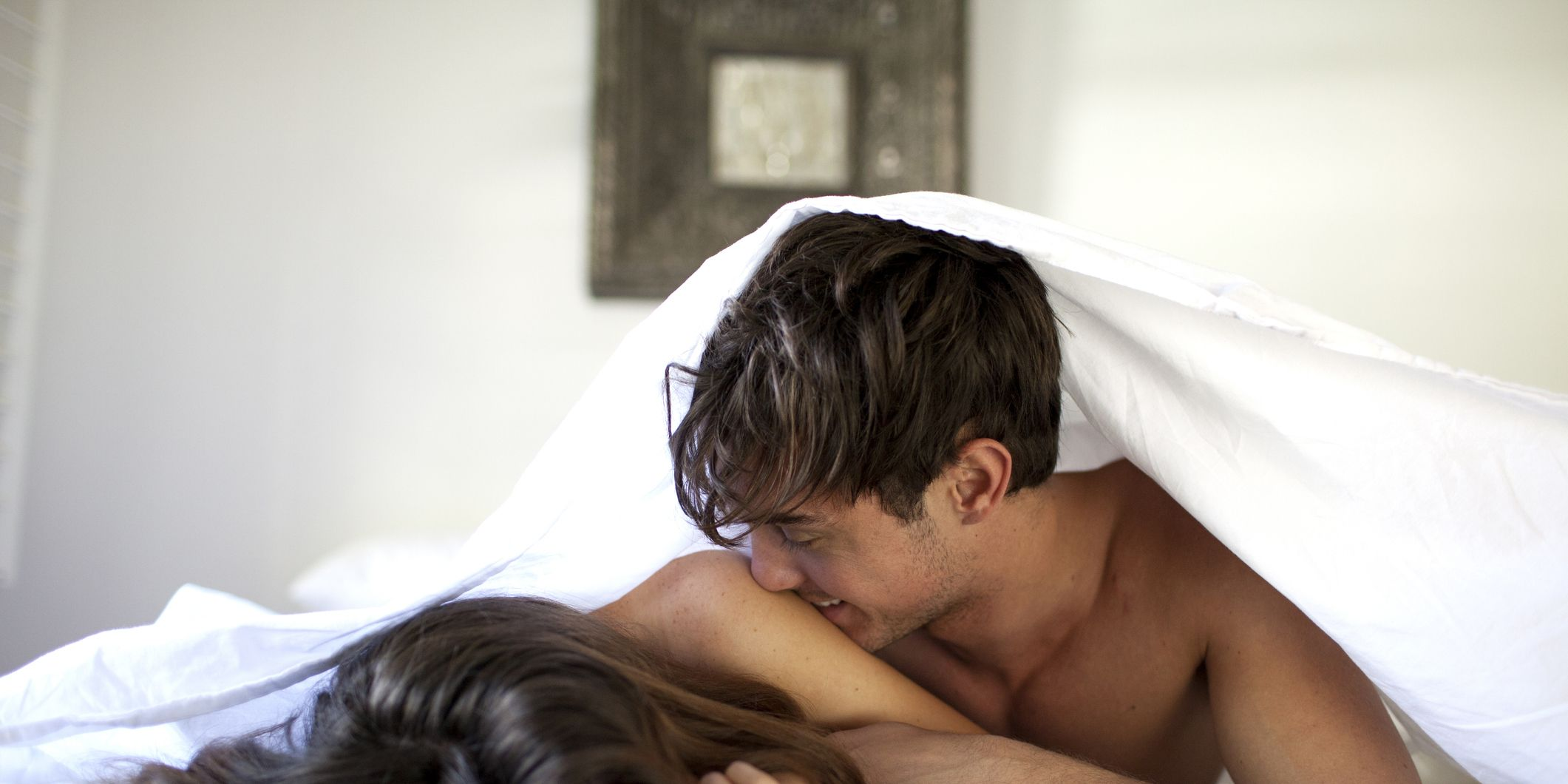 Couple in bed under white sheets kissing