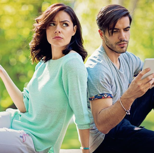 couple in conflict is texting in the park sulking each other