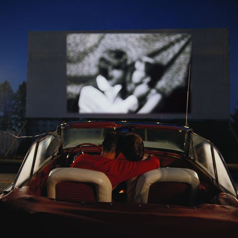 Couple in convertible car, watching film at drive-in (Composite)