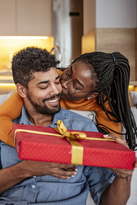 a black couple giving each other a red wrapped gift