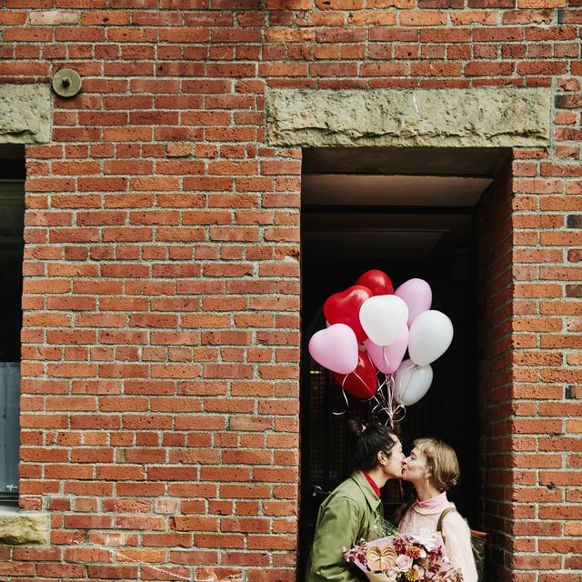 Couple kissing in doorway while on Valentines Day date