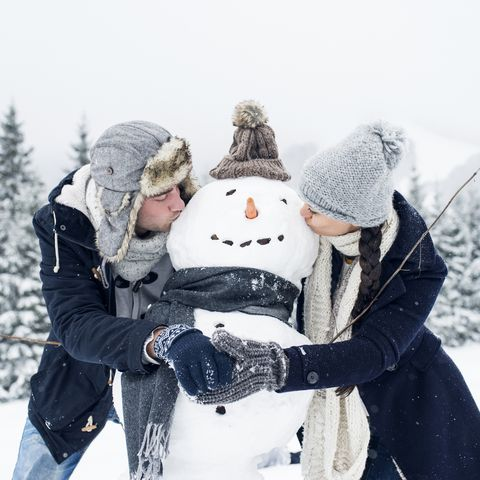 winter date ideas - Couple kissing snowman