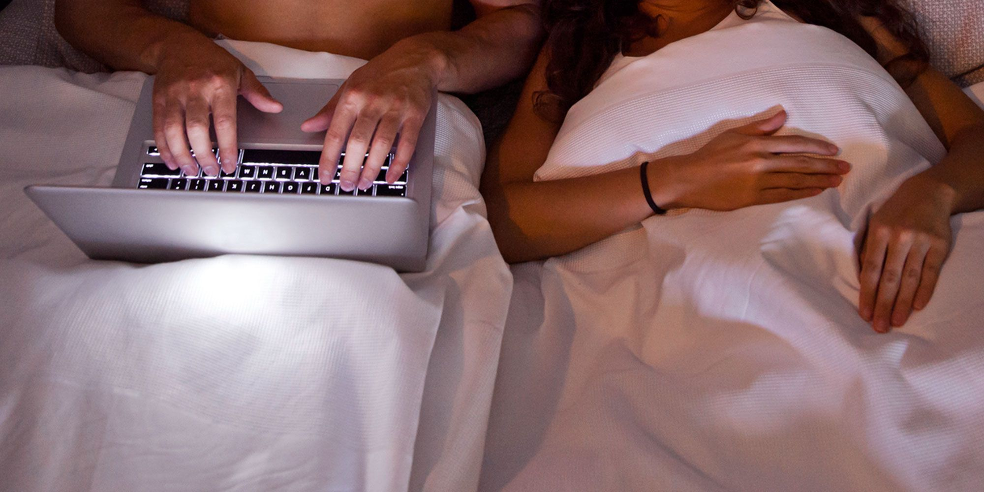 Couple using a laptop in bed together