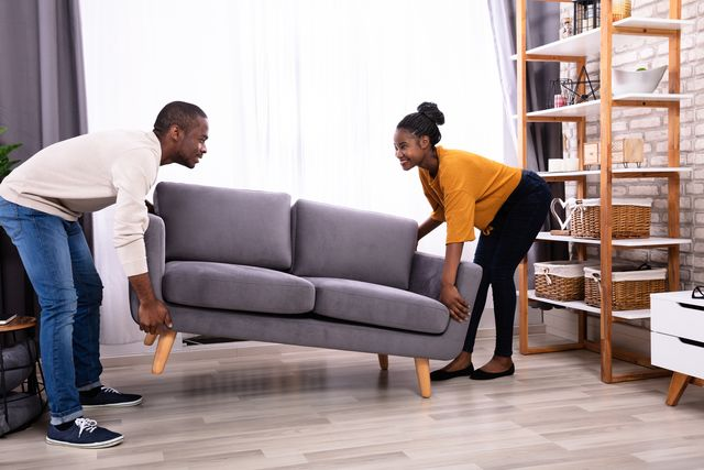 couple lifting sofa in living room