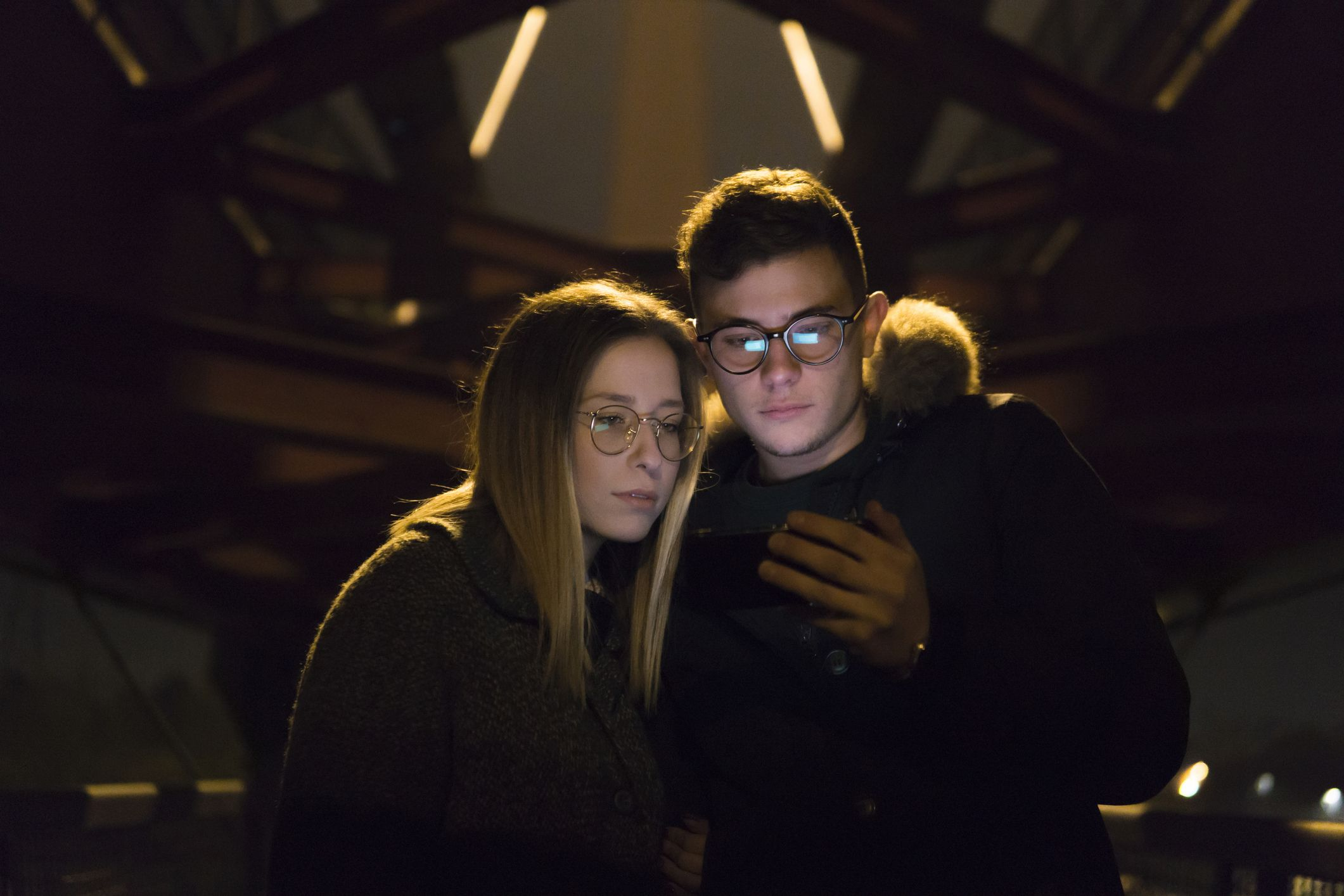 Couple Looking At Mobile Phone under a metal bridge