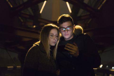 Couple à la recherche de téléphone portable sous un pont métallique