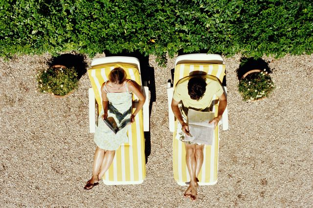 couple lying on sunbeds reading, overhead view