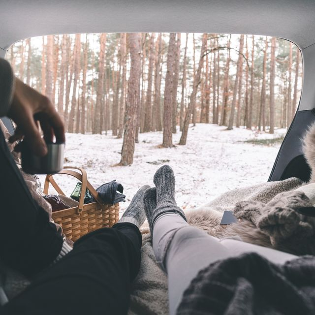 a couple on a winter picnic in their car trunk
