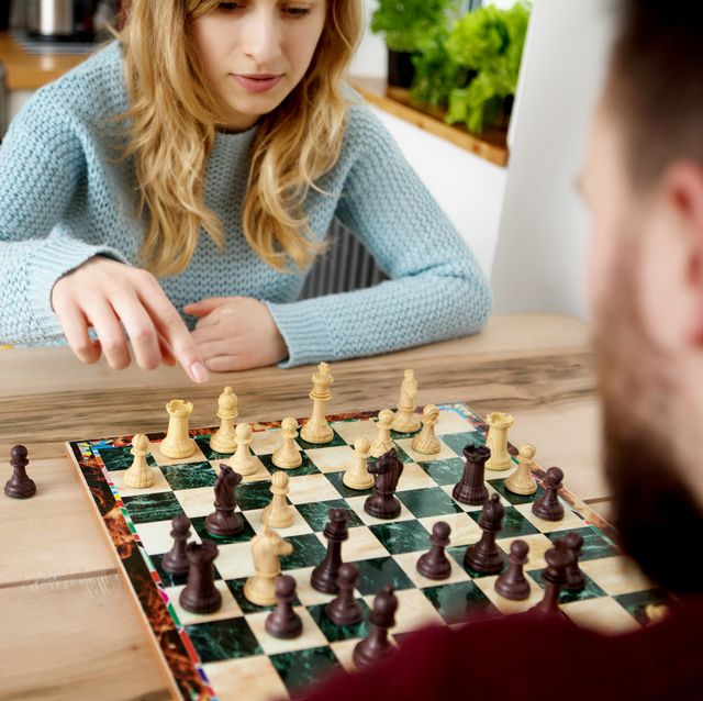 couple playing chess on table at home