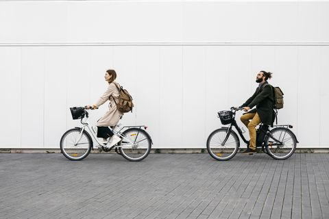 Couple riding e-bikes along a white wall in the city
