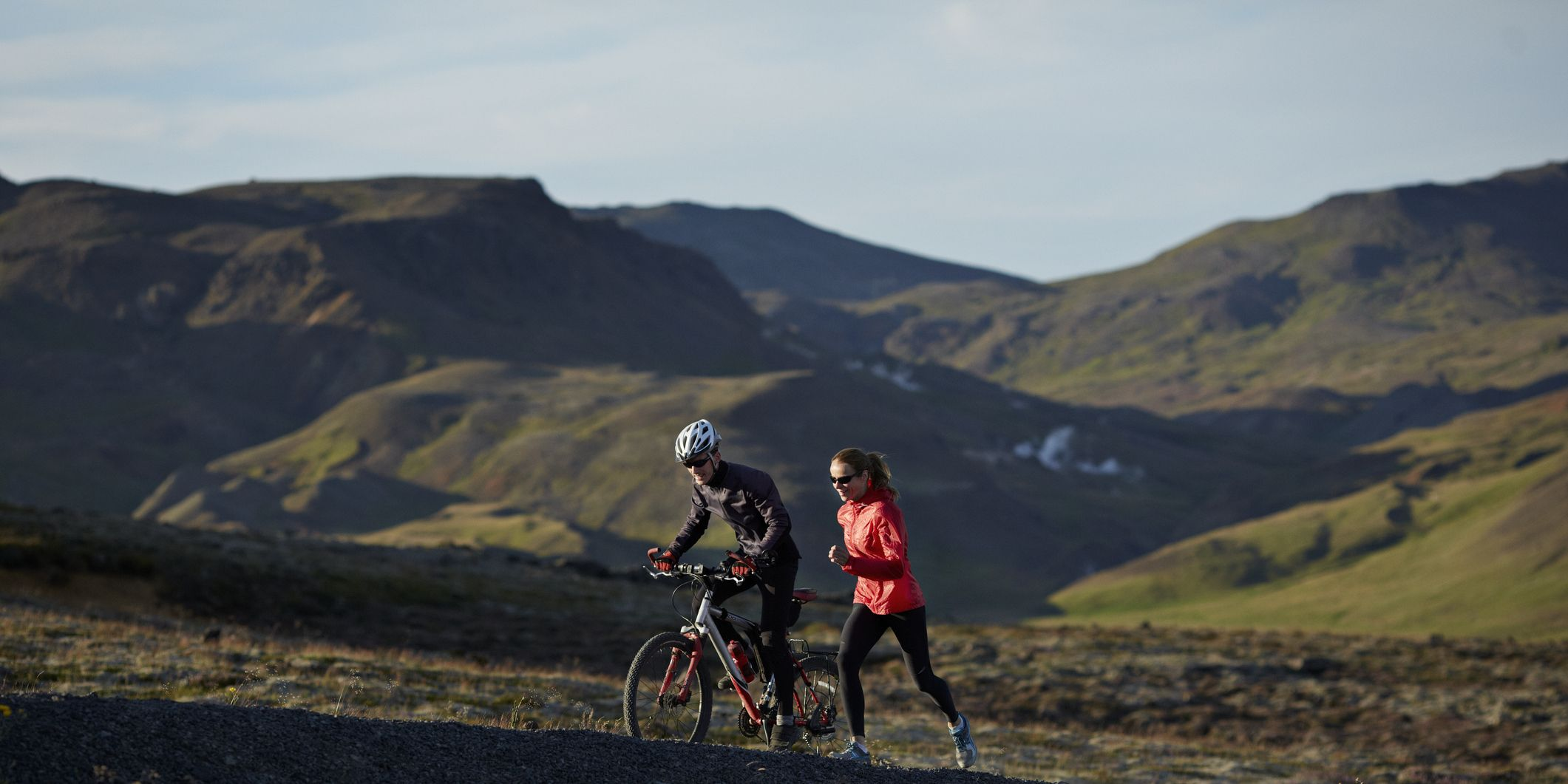 Couple running & biking together on mountain trail