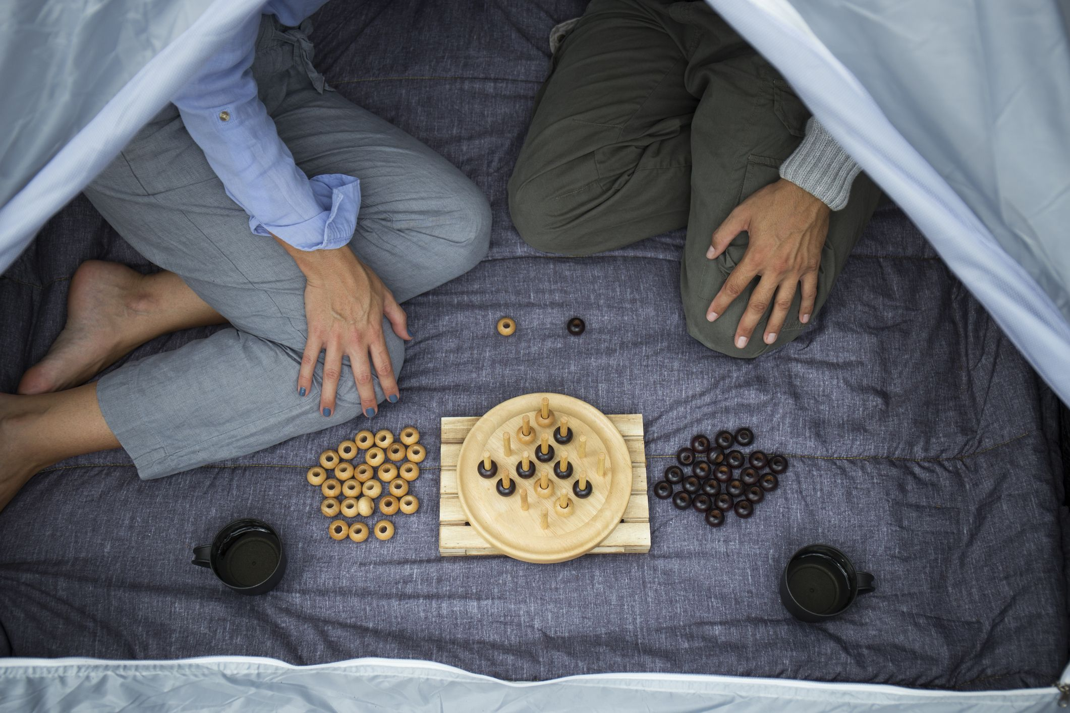 двойка, седнала в палатка, играеща настолна игра, частичен изглед