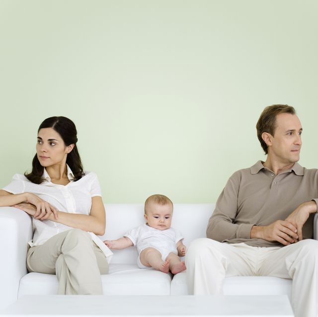 couple sitting on couch with baby between them, both looking away