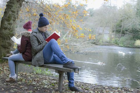 Couple sitting on park bench reading
