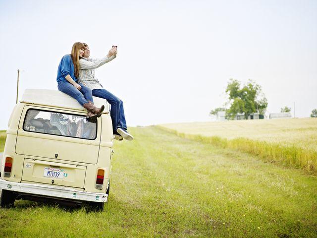 couple sitting on top of van taking photo