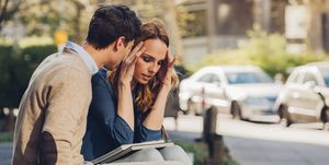 Couple sitting outdoors with woman holding head in hands