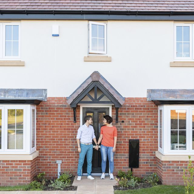 couple standing at doorstep of their home
