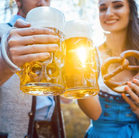 Couple Toasting Beer Glasses While Standing Outdoors