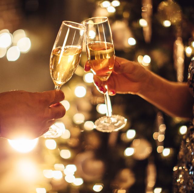 couple holding glasses of champagne in front of christmas tree toasting to each other evening or night