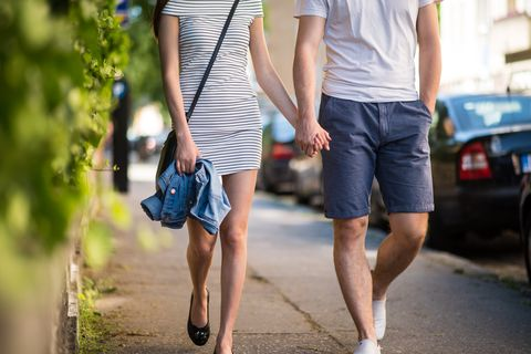 Couple walking on sidewalk with hand in hand