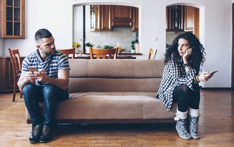 Couple with relationship difficulties sitting on sofa at home
