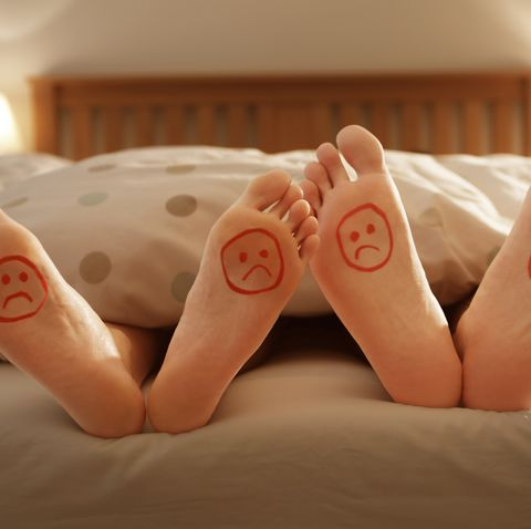 couples unhappy feet in bed