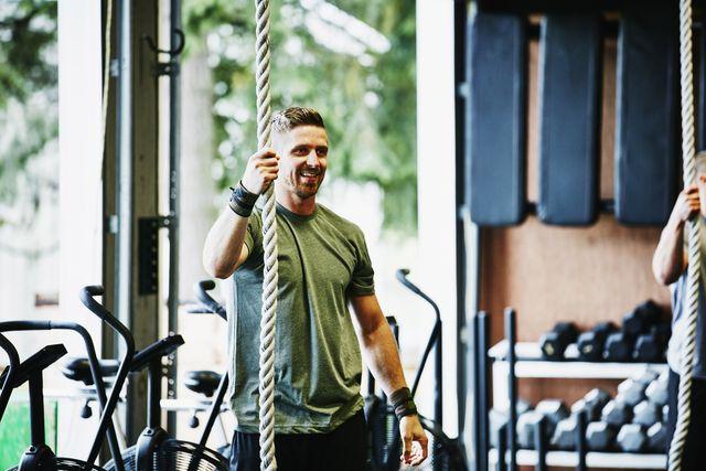 smiling man preparing to climb rope in gym gym during workout