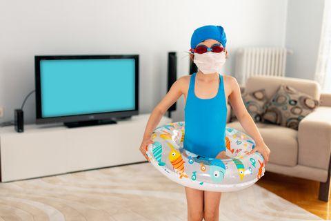 niña con flotador, guante, gafas de buceo y mascarilla en el salón de su casa
