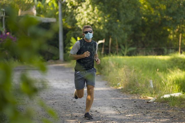 covid 19 deconfinement   young attractive and happy man outdoors in city park doing running workout wearing protective face mask jogging and training after long days of quarantine