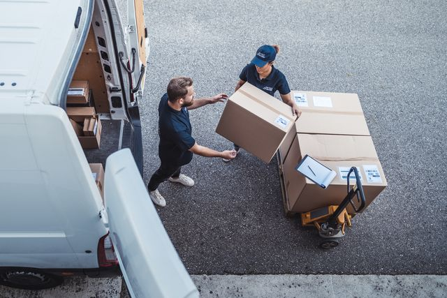 coworkers rushing to load packages in a delivery van