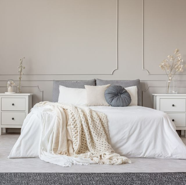 cozy cream colored woolen blanket on king size bed in bright bedroom